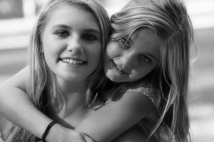 Two girls embracing each other looking at the camera