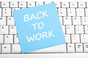 Back to work note on top of a keyboard
