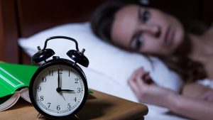Woman with insomnia struggling to sleep with the alarm clock showing 3am