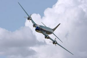 A silver plane flying in the air